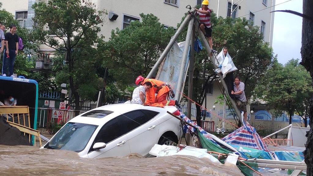 突发暴雨!深圳20名乘客被困公交车顶 消防徒步涉水救援